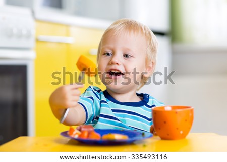 Cute child little boy eating healthy food in kitchen - stock photo