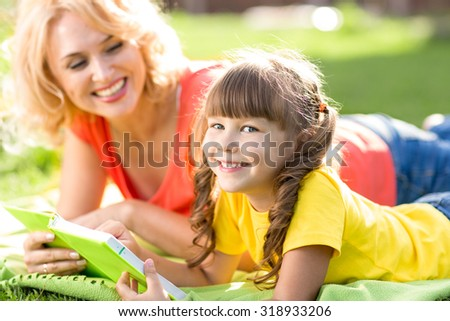 Cute child little girl reading book with her mother and smiling. Summer grass in background.