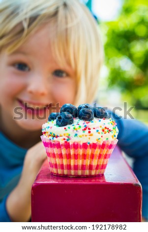 Cute child looking at a delicious cupcake covered in sprinkles and blueberries. Focus is on cupcake - stock photo