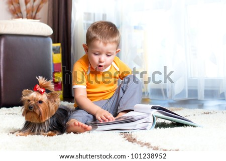 Cute child looking over family photo-album.  Puppy dog york terrier sitting near.