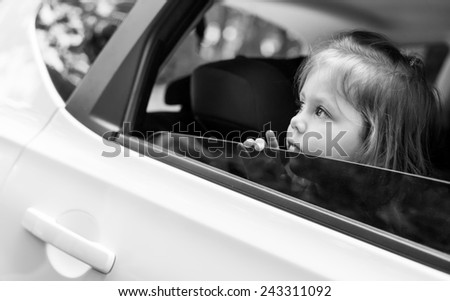 Cute child looks out the window of the car in the summer ( black and white ) - stock photo