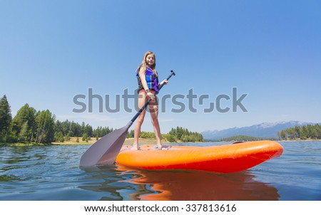 Cute Child paddling on a Stand Up Paddle board on a beautiful, peaceful Mountain lake. Low angle view - stock photo