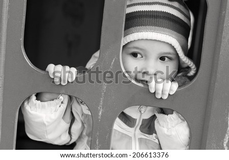 cute child playing at the playground ( black and white ) - stock photo