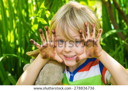 Cute child playing in garden with dirty hands - stock photo