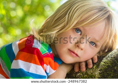 Cute child relaxing deep in thought outdoors on a tree - stock photo