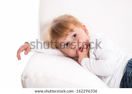 Cute child - shy girl lying on white sofa sucking thumb or finger