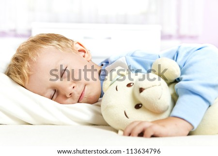 Cute child sleeping in bed - stock photo