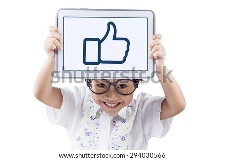 Cute child smiling on the camera while holding a tablet to show a thumb up icon, isolated on white background - stock photo