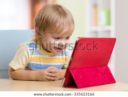 Cute child toddler boy with tablet pc sitting at table in home - stock photo