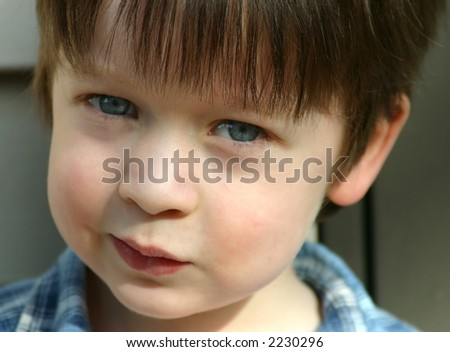 Cute child with blue eyes, close-up, and looking mischievous - stock photo
