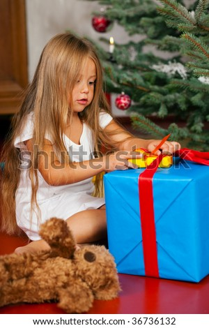 Cute Child with teddy bear toy finding her Christmas present in the morning still in her sleepwear and unwrapping it - stock photo