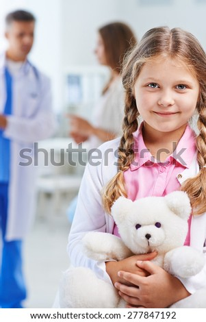 Cute child with white teddy looking at camera while doctor talking to her mother on background - stock photo