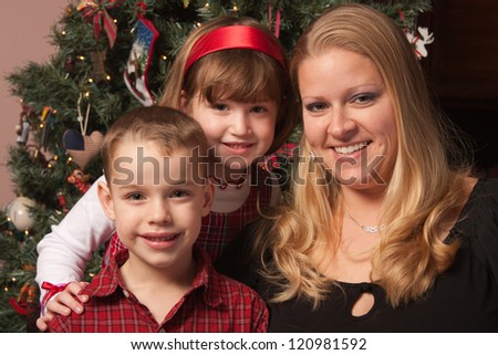 Cute Children and Mother Posing for a Portrait in Front Of Holiday Tree.
