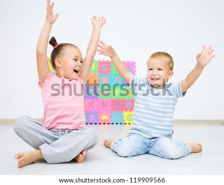 Cute children are sitting on floor in preschool rising their hands up - stock photo
