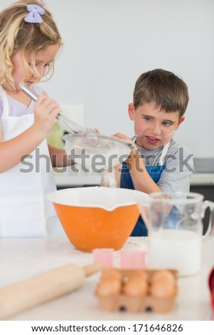 Cute children baking cookies together at kitchen counter