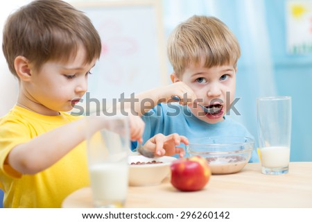cute children eat healthy food enjoying breakfast - stock photo