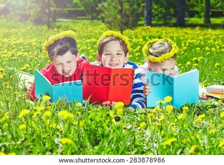 Cute children in dandelion wreaths reading on lawn - stock photo