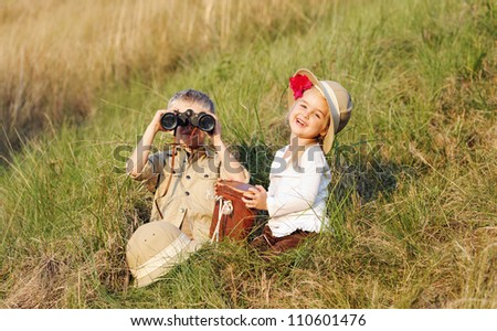 cute children playing pretend safari game together outdoors. happy brother and sister - stock photo