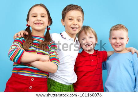 Cute children smiling at camera, isolated on blue background - stock photo