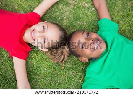 Cute children smiling at camera outside on the grass in the park - stock photo