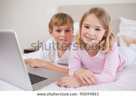 Cute children using a notebook in a bedroom - stock photo