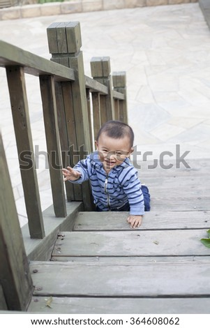 Cute Chinese baby boy crawling on stairs, shot in Beijing, China - stock photo