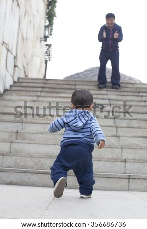 Cute Chinese baby boy learning walking, encouraged by his father, real people - stock photo