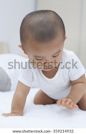 Cute Chinese baby boy playing in bed - stock photo