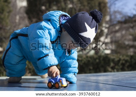 Cute Chinese baby boy playing on a table tennis table, shot in Beijing, China - stock photo