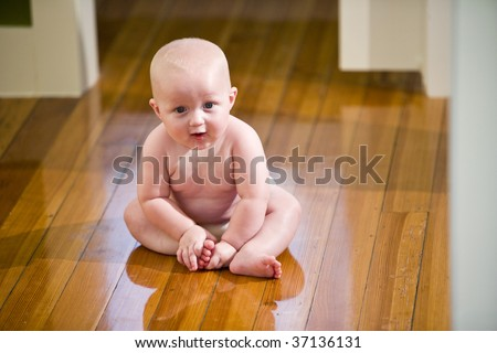 Cute chubby seven month old baby wearing diaper sitting on floor - stock photo