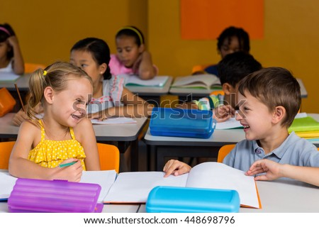 Cute classmates laughing in classroom