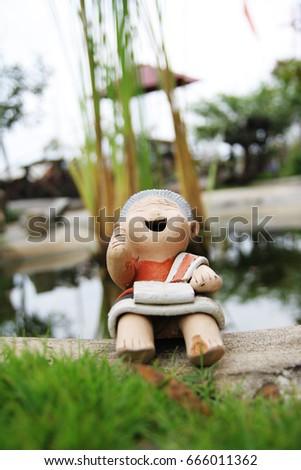 Cute Clay Doll In The Garden