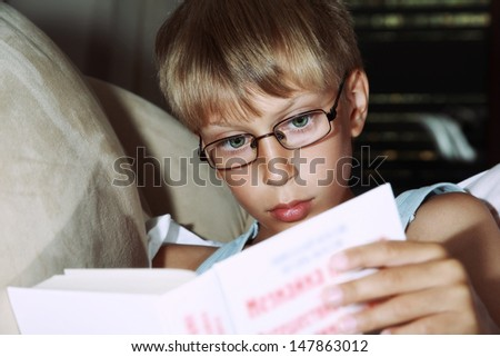 Cute clever blond boy wearing an undershirt and glasses reads a hardcover book on a beige sofa - stock photo