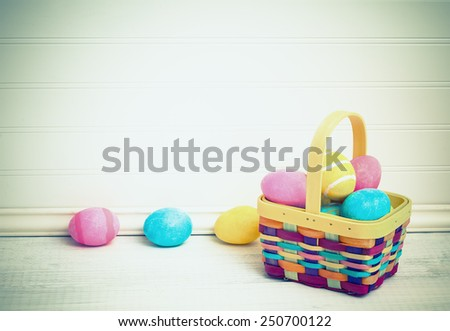 Cute, Colorful Overflowing Easter Basket with Eggs Dyed by Kids on White Painted Board Table and Background with empty, blank room or space for copy, text, your words. Horizontal vintage instagram  - stock photo