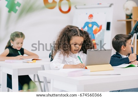 Cute concentrated multiethnic schoolkids studying with exercise books and digital tablet in class