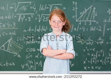 Cute confident pretty young girl in class standing with her back to a blackboard covered in mathematical equations smiling at the camera with folded arms - stock photo