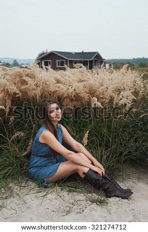 Cute countryside lady with brown hair posing against ranch house. She sits in tall grass against rural scape. She wears jeans dress. House has one floor. It is made of wood and is painted brown.