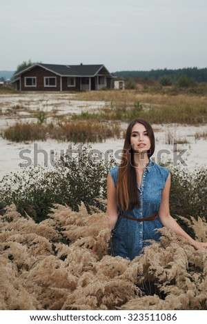 Cute countryside lady with brown hair posing against ranch house. She stands in tall grass against rural scape. She wears jeans dress.   - stock photo