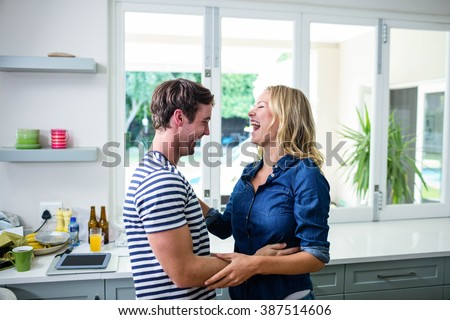 Cute couple dancing and laughing in the kitchen - stock photo