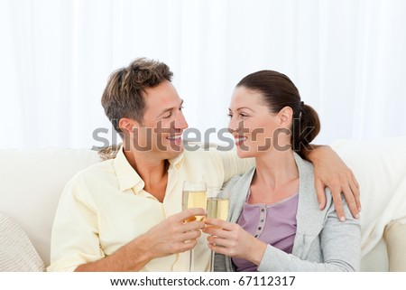 Cute couple drinking champagne while relaxing on the sofa at home - stock photo