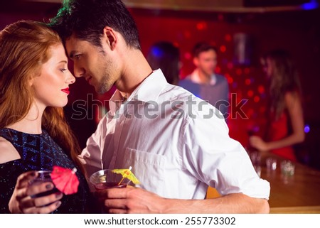 Cute couple drinking cocktails together at the nightclub - stock photo