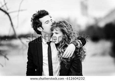 Cute couple embraces black and white portrait of the stylish young man in a suit