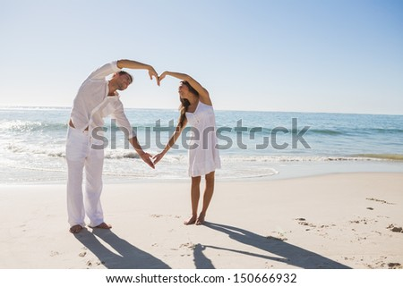 Cute couple forming heart shape with arms at the beach - stock photo