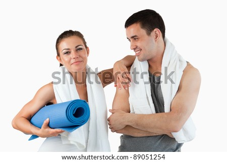 Cute couple going to practice yoga against a white background