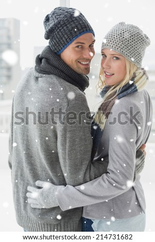 Cute couple in warm clothing hugging smiling at camera against snow falling - stock photo