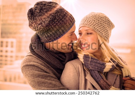 Cute couple in warm clothing smiling at each other on a chilly day - stock photo