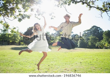 Cute couple jumping in the park together on a sunny day - stock photo