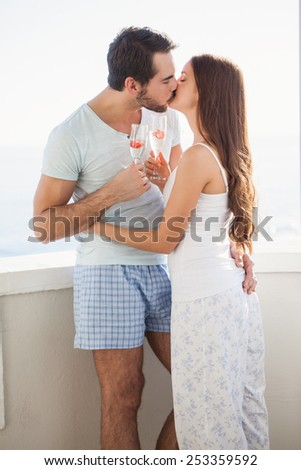 Cute couple kissing while toasting with champagne on their balcony - stock photo