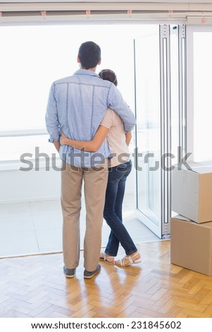 Cute couple looking out the window in their new home - stock photo