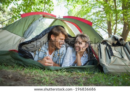 Cute couple lying in their tent smiling at each other on a sunny day